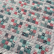 Straight line and circle quilting in 16 patch with gray sashing