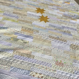 Custom quilting on low volume strip quilt with gold stars