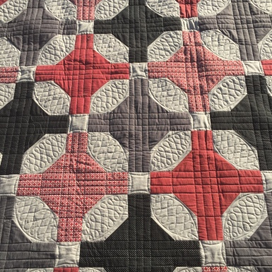 Custom quilting on a red and black nine patch variation