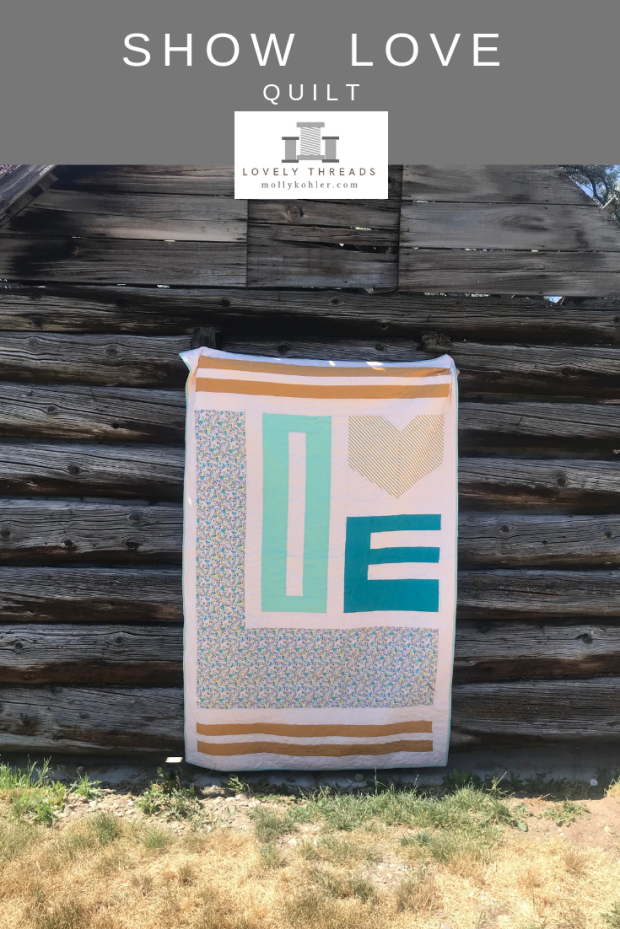 Show Love quilt in front of pioneer cabin